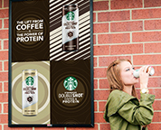 Outdoor advertising of coffee drink with woman drinking coffee.