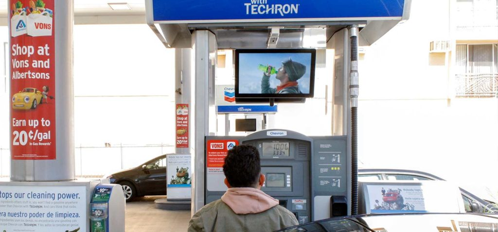 Person looking at a gas pump ad.