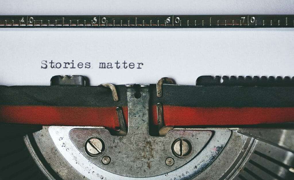 """A typewriter with a piece of paper that says """"stories matter"""" on it."""